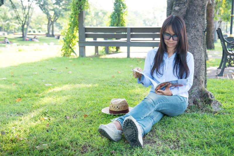 Happy woman enjoy and relax with the nature. Young beautiful woman sitting under the big tree royalty free stock photos