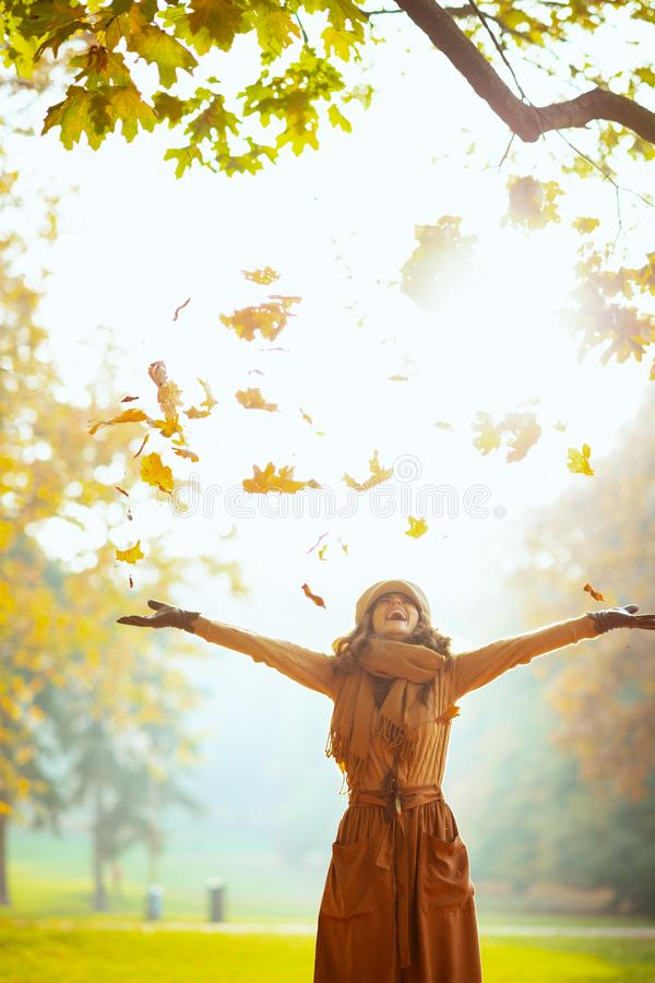Happy woman enjoying autumn and catching falling yellow leaves royalty free stock image
