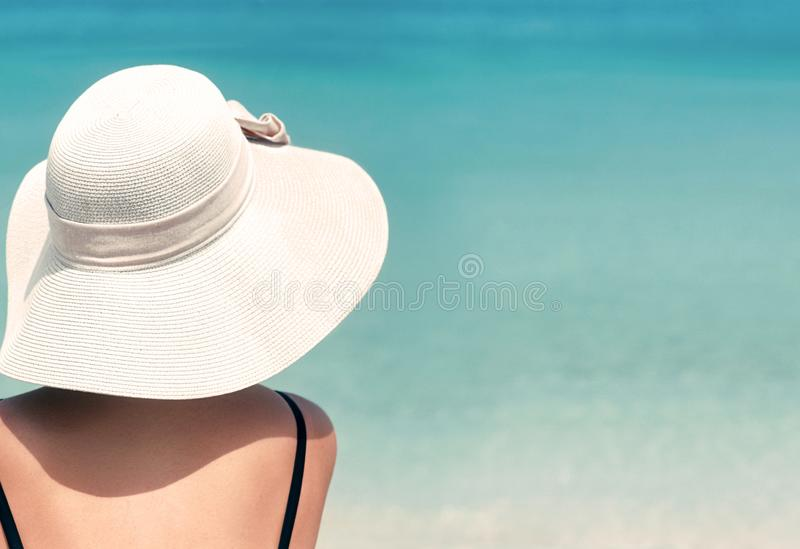 Happy woman enjoying beach relaxing joyful in summer by tropical blue water. Beautiful bikini model happy on travel wearing beach stock photography
