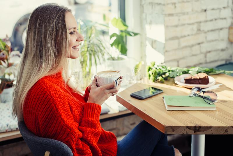 Happy woman enjoying cappuccino coffee in a cafeteria stock images