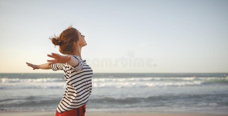 Happy woman enjoying freedom with open hands on sea stock photos