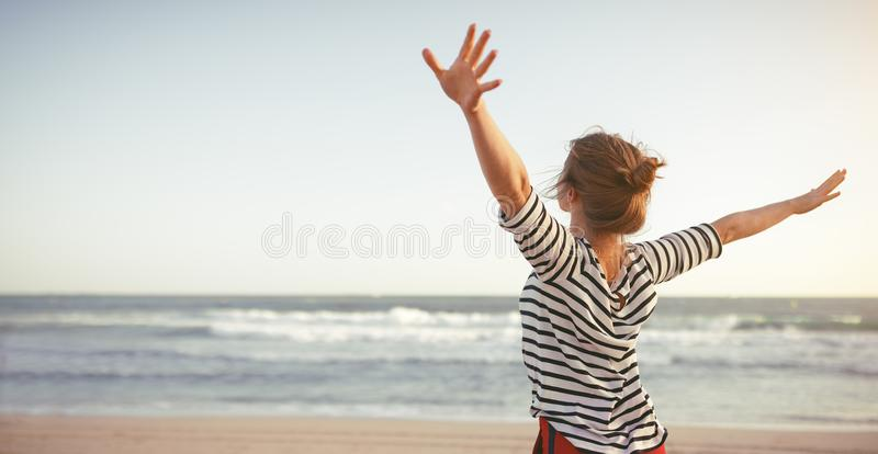 Happy woman enjoying freedom with open hands on sea. Happy young woman enjoying freedom with open hands on sea royalty free stock photo