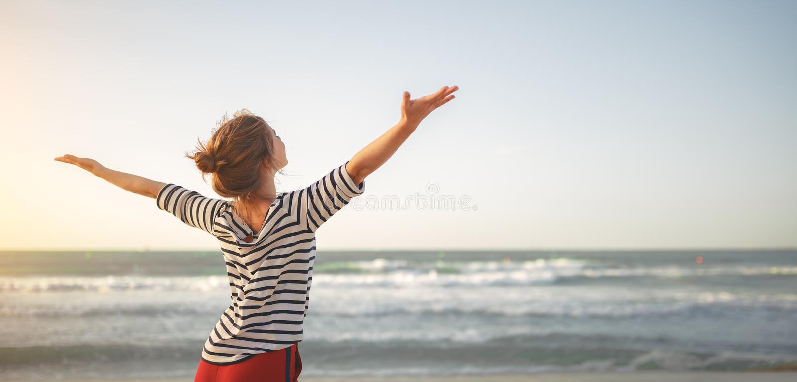 Happy woman enjoying freedom with open hands on sea. Happy young woman enjoying freedom with open hands on sea royalty free stock image