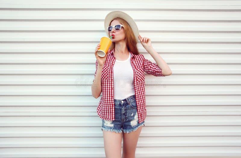 Happy woman enjoying fresh orange juice in summer round straw hat, checkered shirt, shorts on white wall royalty free stock images