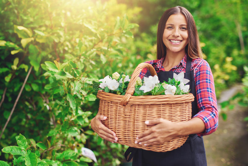 Happy woman enjoying her work at the nursery royalty free stock image