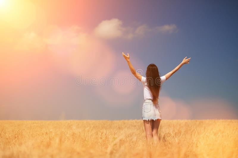 Happy woman enjoying the life in the field Nature beauty, blue cloudy sky and colorful field with golden wheat. Outdoor lifestyle. stock photo