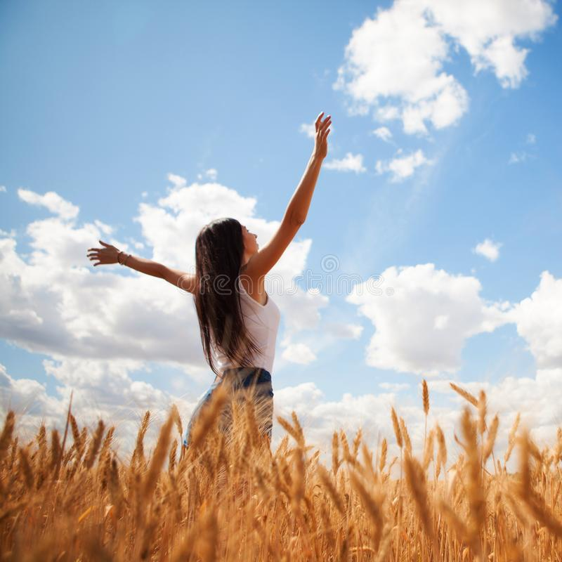 Happy woman enjoying the life in the field. Nature beauty, blue sky,white clouds and field with golden wheat. Outdoor lifestyle. Freedom concept. Woman jump in royalty free stock images