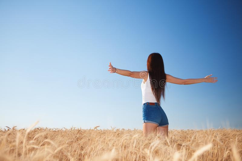 Happy woman enjoying the life in the field. Nature beauty, blue sky,white clouds and field with golden wheat. Outdoor lifestyle. royalty free stock images