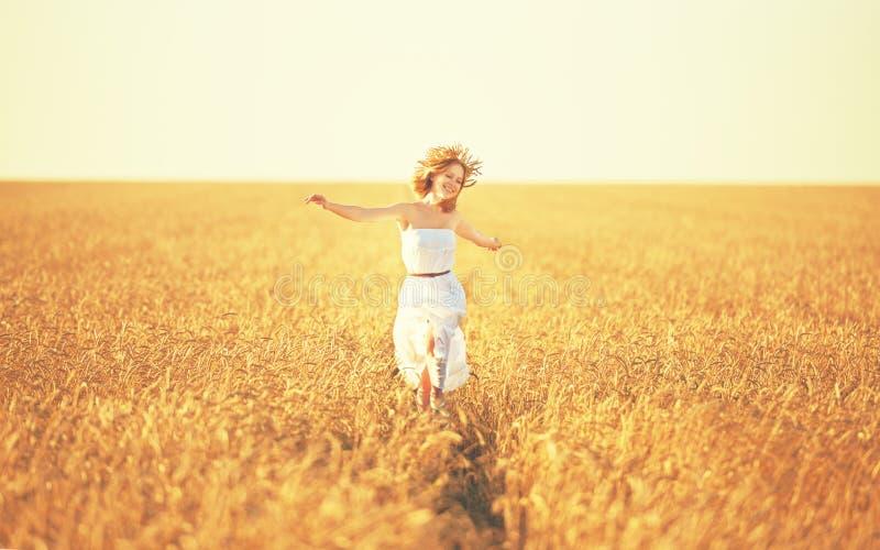 Happy woman enjoying life in golden wheat field stock image