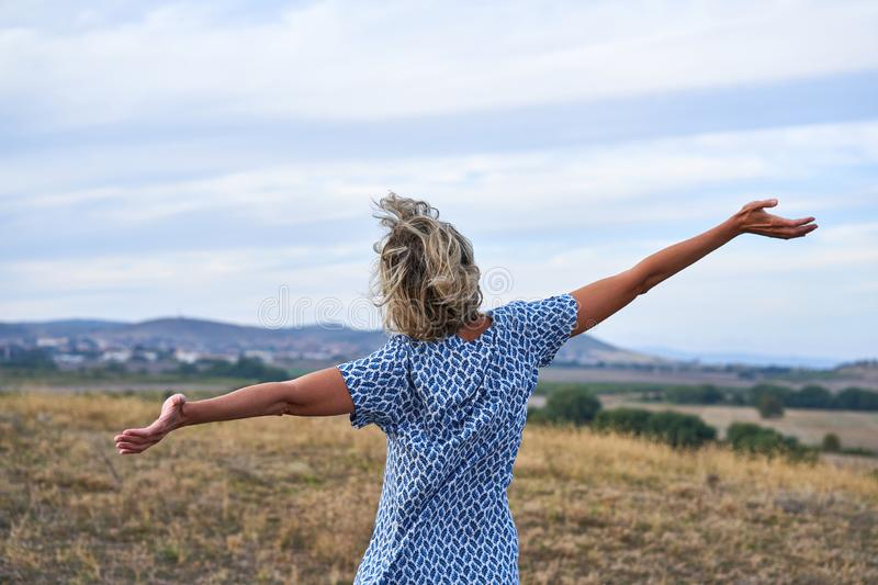 Happy woman enjoying outdoors with arms spreaded royalty free stock images