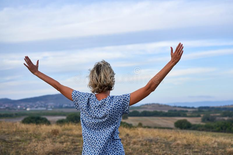 Happy woman enjoying outdoors with arms spreaded stock photo