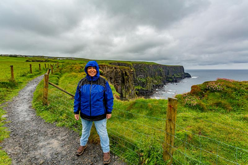 Happy woman enjoying a rainy day on the coastal walk route from Doolin to the Cliffs of Moher. Geosites and geopark, Wild Atlantic Way, spring day in the stock images