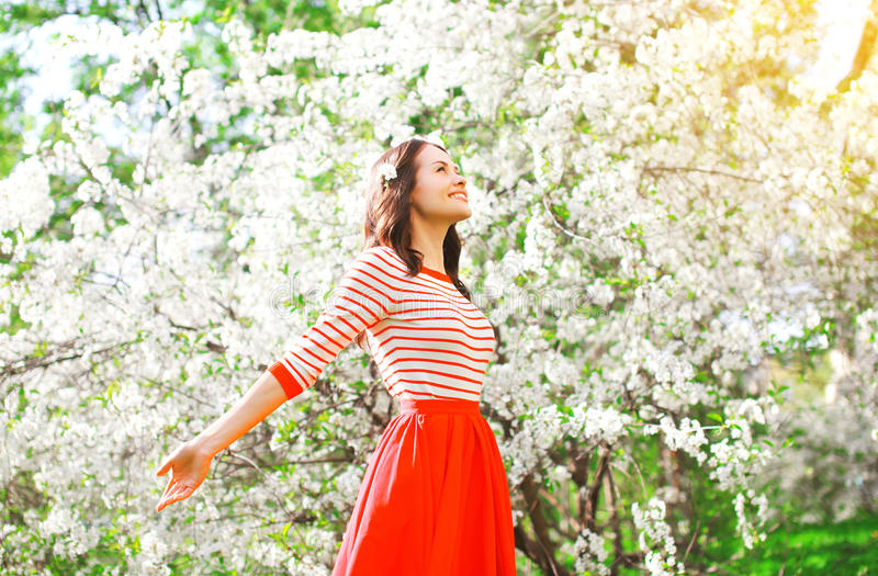 Happy woman enjoying smell flowers over spring garden stock photography