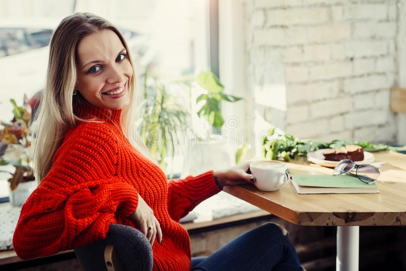 Happy woman enjoying some coffee in a restaurant stock images