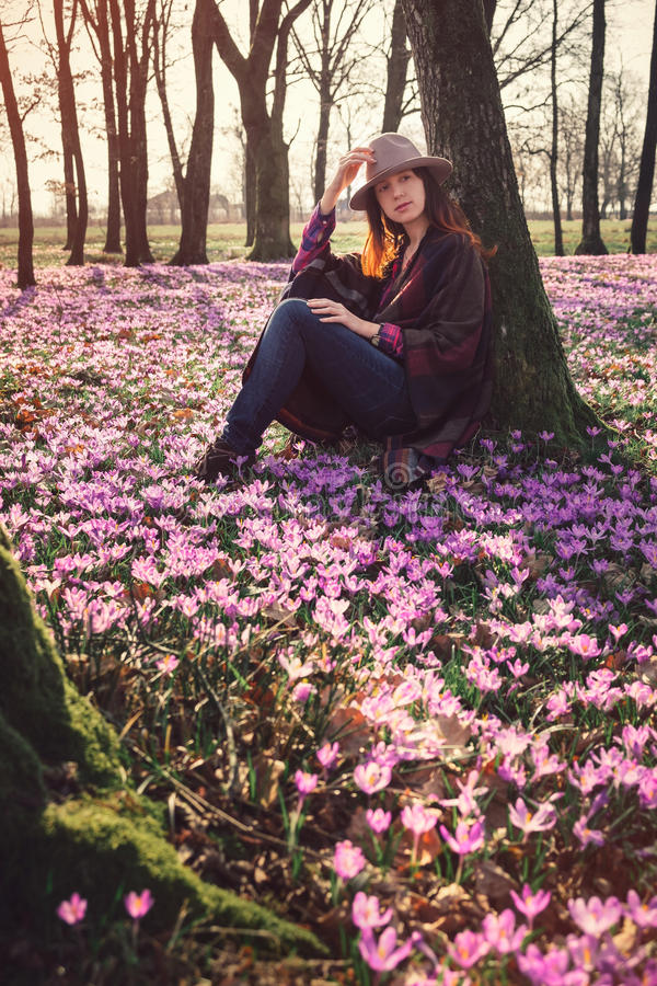 Happy woman enjoying the spring nature and crocus flowers. Tender woman woman walking among beautiful landscape with purple carpet of blossoming crocus flowers stock photos