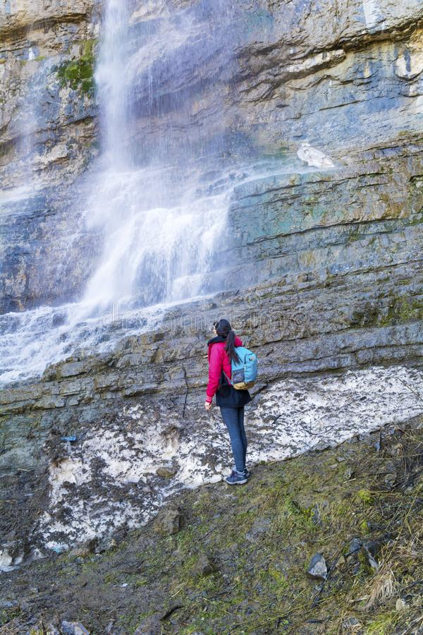 Hiker Woman Looking Big Waterfall. Happy woman enjoying the stunning view in the spring mountain with lush waterfall royalty free stock images