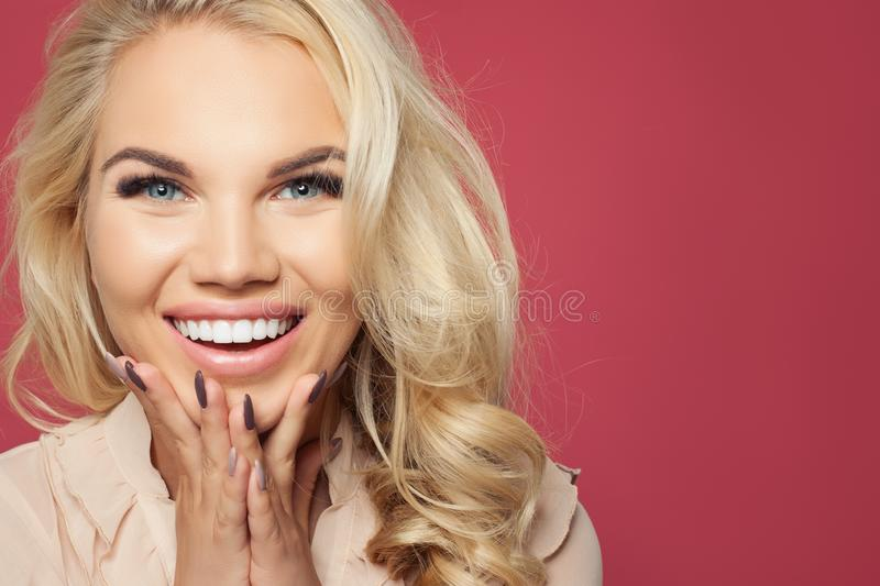 Happy woman face closeup portrait. Laughing girl on pink background, pretty face royalty free stock photography