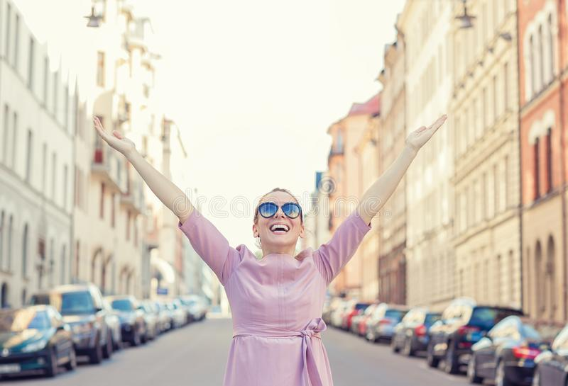 Happy woman feeling free with arms wide open in the city back light royalty free stock image