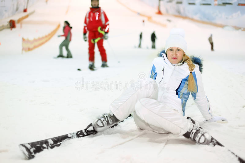 Happy woman fells on ski. Happy blonde woman dressed in white sports clothes fells on ski in indoor ski stock photos