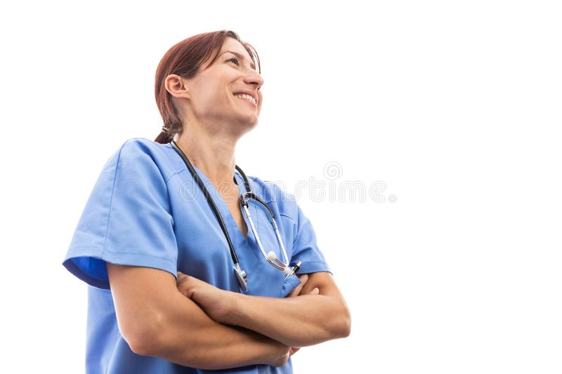 Happy woman female nurse or doctor looking up and smiling. With arms crossed as beautiful cheerful hospital worker concept isolated on white background stock image