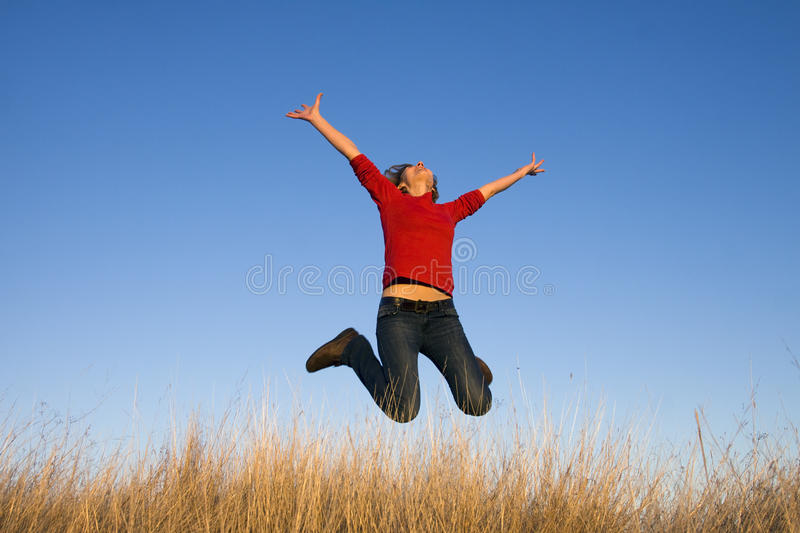 Happy woman in field. Jumping woman on a sunny day against a blue sky royalty free stock photos