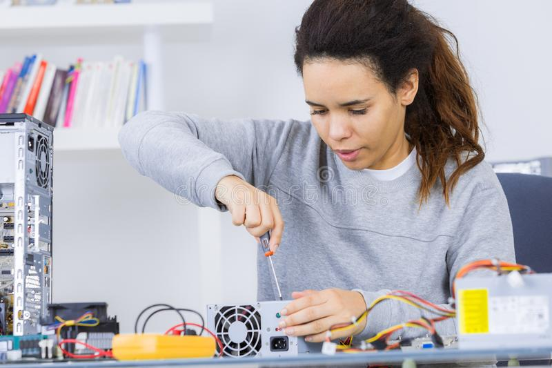Happy woman fixing computer at desk at work royalty free stock photography