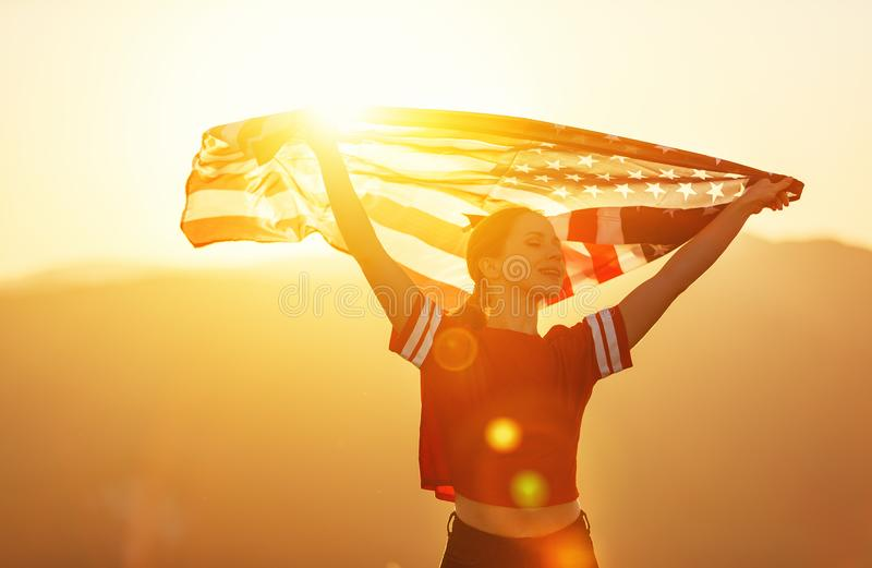 Happy woman with flag of united states enjoying the sunset on na. Young happy woman with flag of united states enjoying the sunset on nature stock images