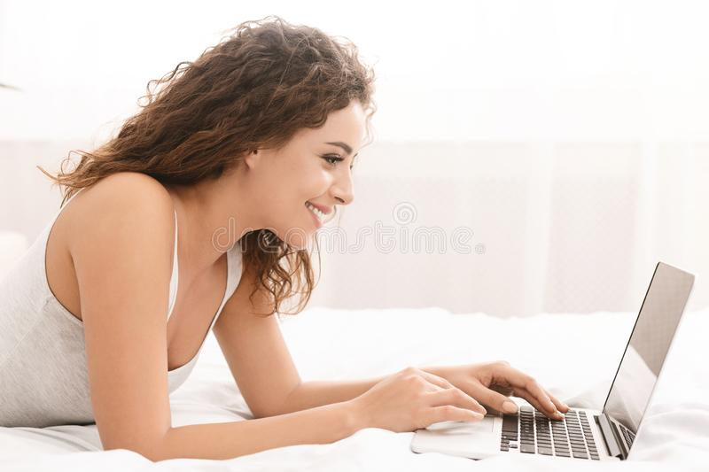 Happy woman flirting online on laptop in bed royalty free stock images