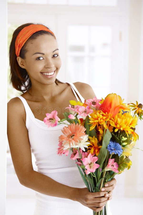 Happy woman with flower bouquet. Portrait of happy woman standing with flower bouquet handheld, smiling at camera stock image