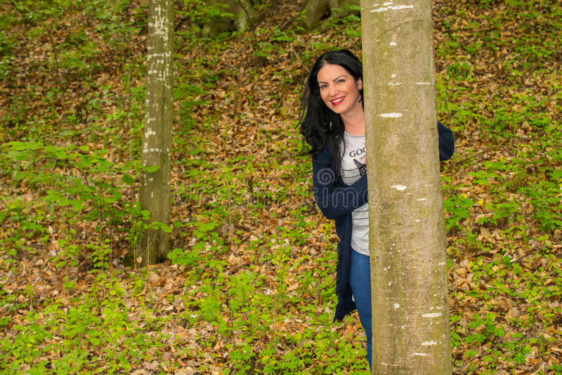 Happy woman in forest. Woman is hiding behind the tree in the forest stock photo