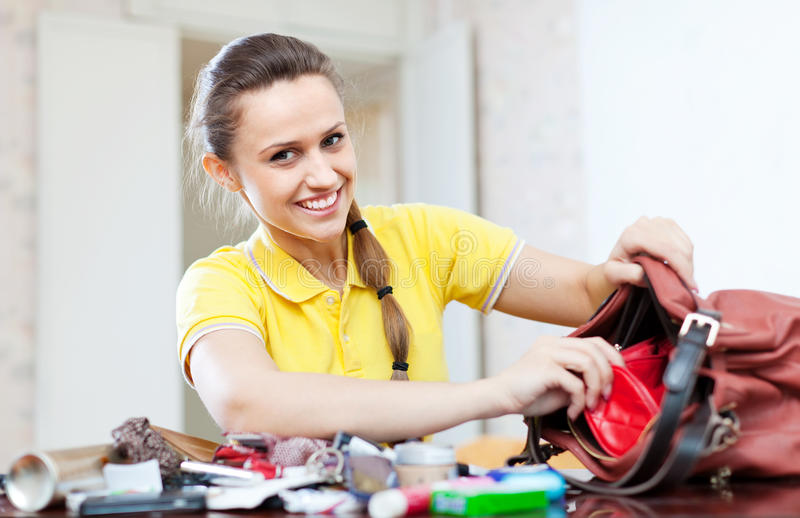 Happy woman found thing in handbag stock photography