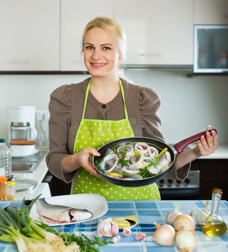 Happy woman with frying pan. Happy woman with fish in frying pan royalty free stock photo