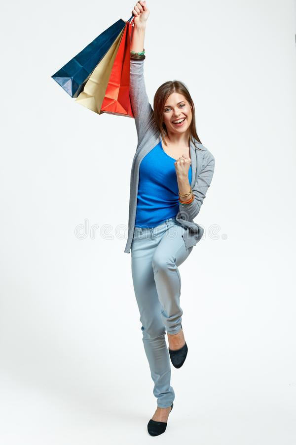Happy woman full body portrait with shopping bag. On isolated studio background royalty free stock photos
