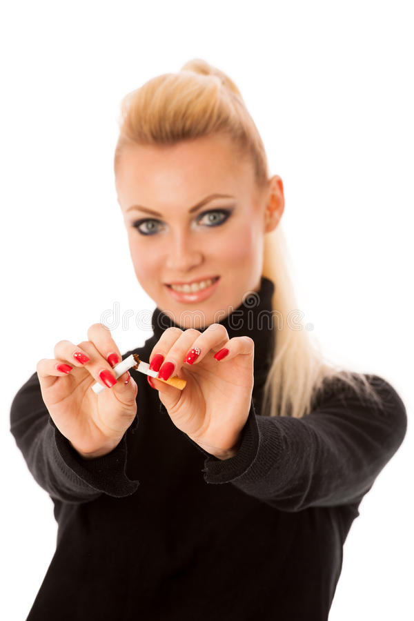 Happy woman gesturing quitting stinky unhealhy habbit by breaking cigarette decided to quit smoking. royalty free stock photography