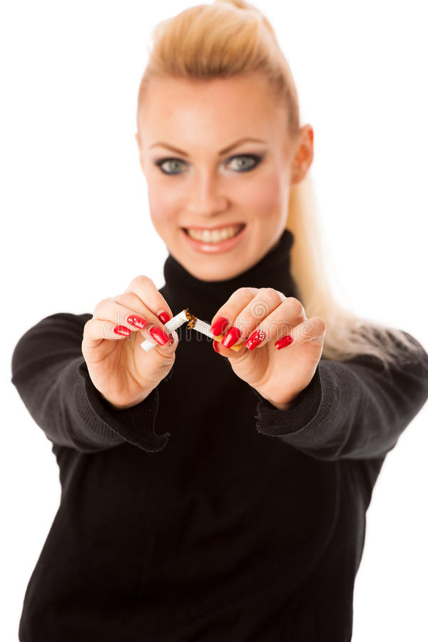 Happy woman gesturing quitting stinky unhealhy habbit. By breaking cigarette decided to quit smoking stock photography