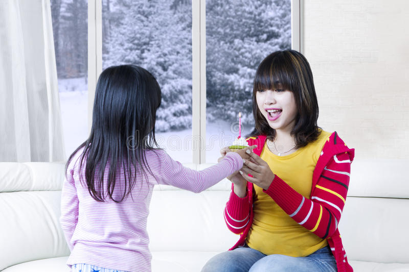 Happy woman gets cupcake. Happy young women gets a cupcake from her daughter with a candle, shot in the living room stock photo