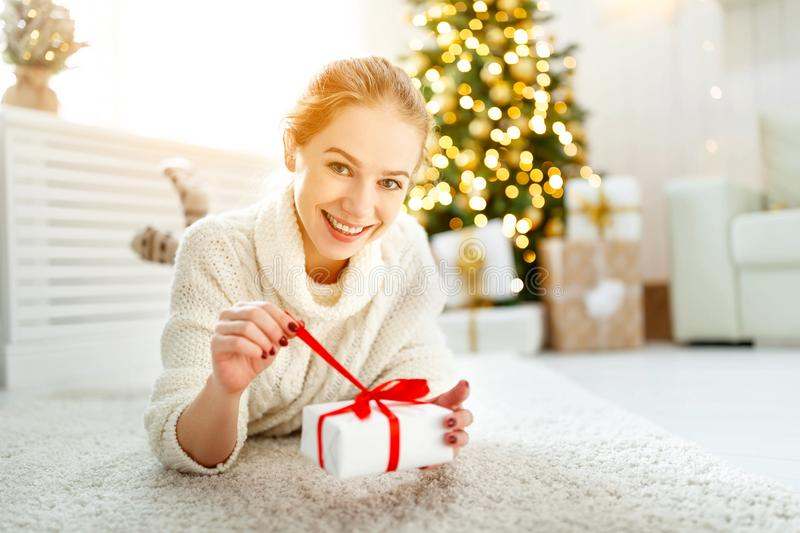 Happy woman with gift at morning near Christmas tree. Happy woman with gift at morning near a Christmas tree royalty free stock images