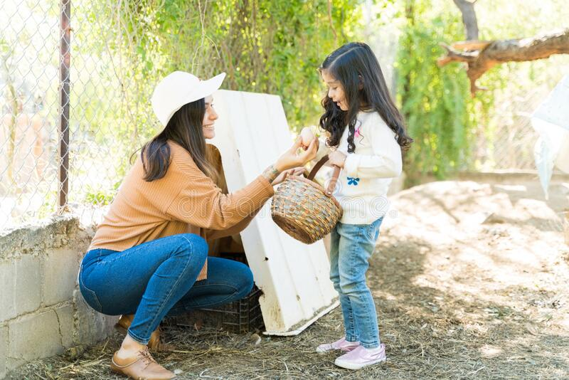 Happy Woman Giving Egg To Girl At Farm royalty free stock photos