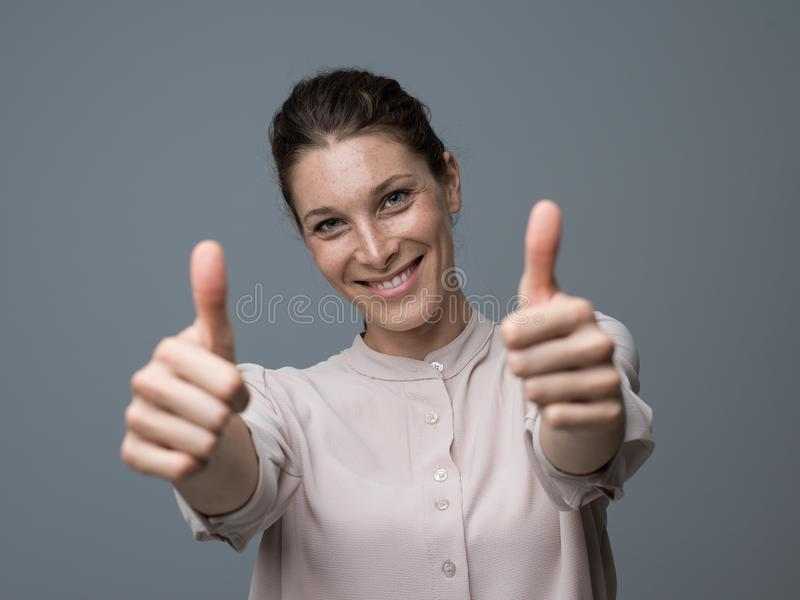 Happy woman giving a thumbs up stock image