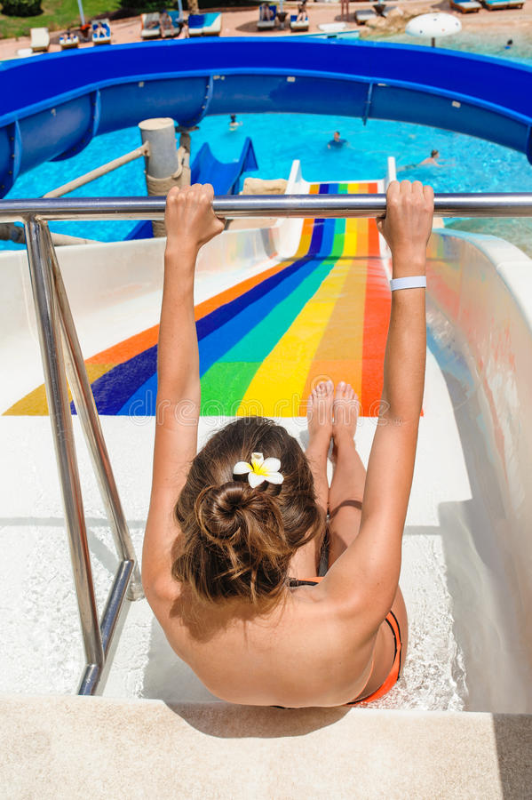 Happy woman going down a water slide at park. Happy woman going down a water slide at a water park royalty free stock photography
