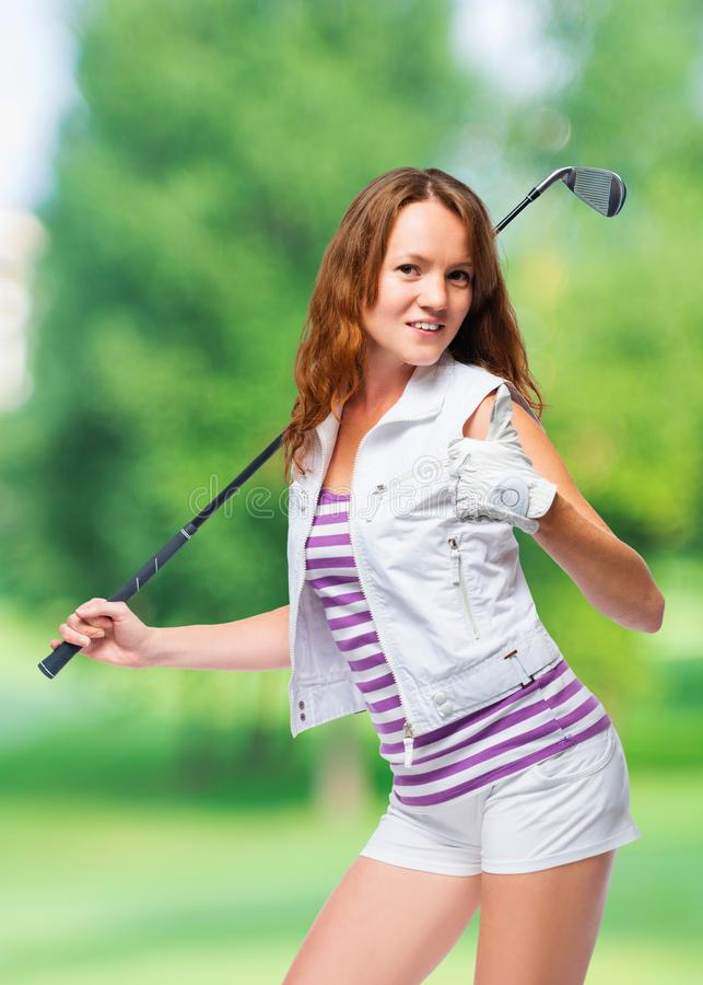 Happy woman with a golf club holds a thumb up royalty free stock photos