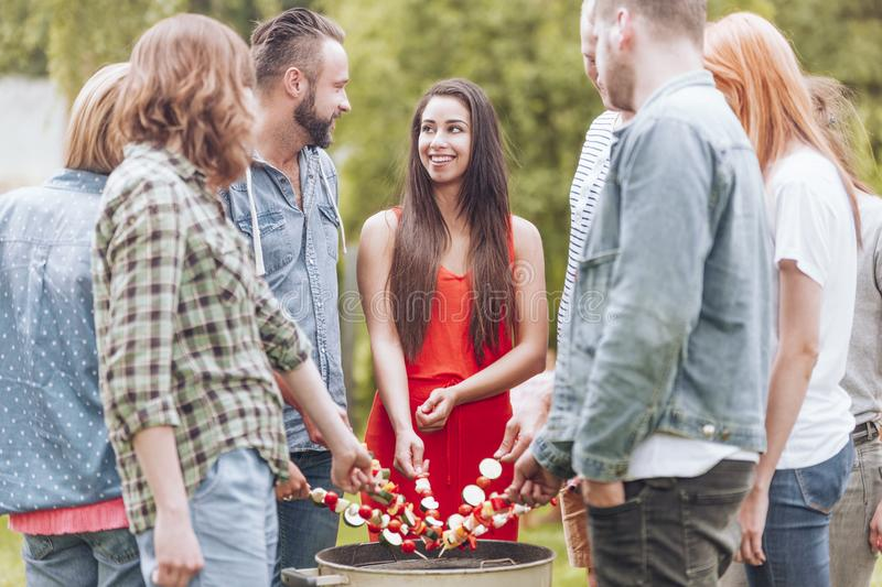 Happy woman grilling shashlik with friends during birthday party in the garden. Happy women grilling shashlik with friends during birthday party in the garden stock photo