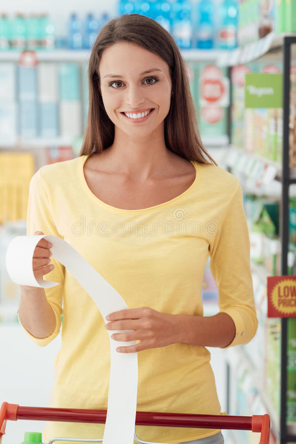 Happy woman with grocery receipt. Young smiling woman shopping at the supermarket and checking a long grocery receipt royalty free stock photo