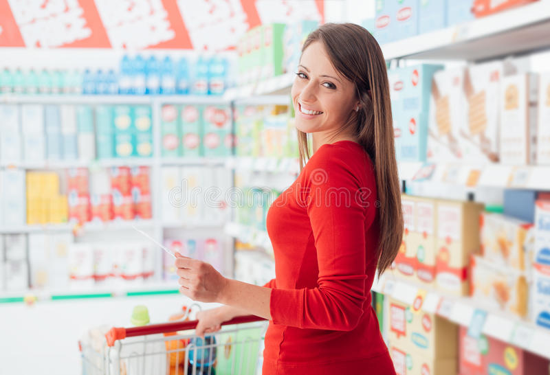 Happy woman at the grocery store. Happy young woman shopping at the grocery store, she is holding a list and pushing a cart, lifestyle and retail concept stock photos