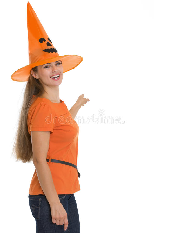 Happy woman in Halloween hat pointing on back. Happy young woman in Halloween hat pointing on back stock photo