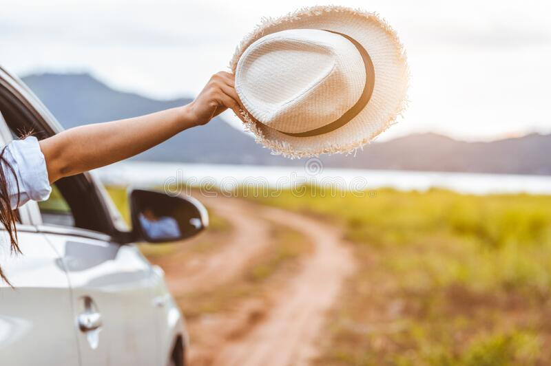 Happy woman hand holding hat outside open window car with meadow and mountain lake background. People lifestyle relaxing as. Traveler on road trip in holiday royalty free stock photography
