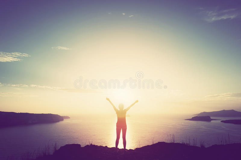 Happy woman with hands up on cliff over sea and islands at sunset royalty free stock image
