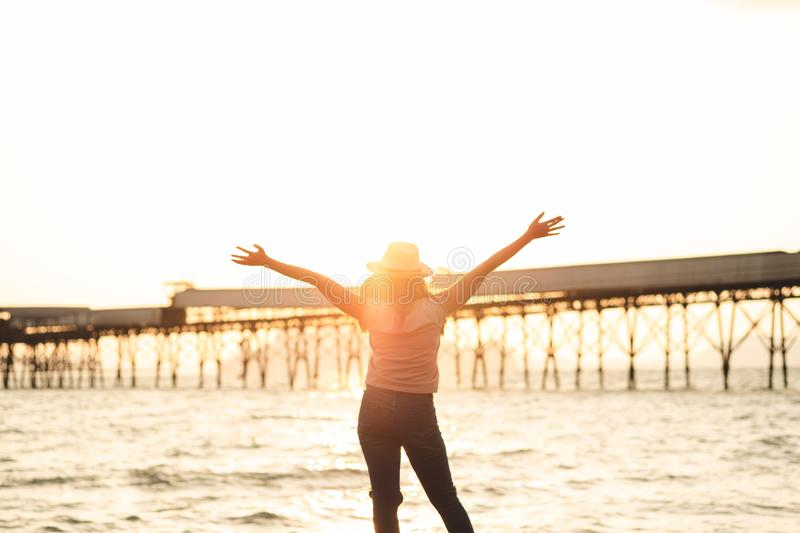 Happy woman with hands up standing on sunset beach in summer wit stock photos