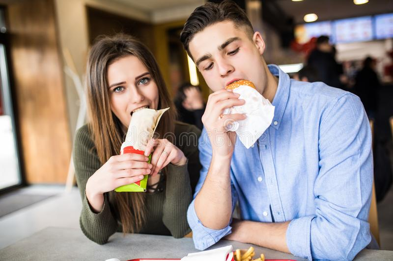 Happy woman and a handsome man are enjoying their delicious and tasty burgers in the burger royalty free stock photos