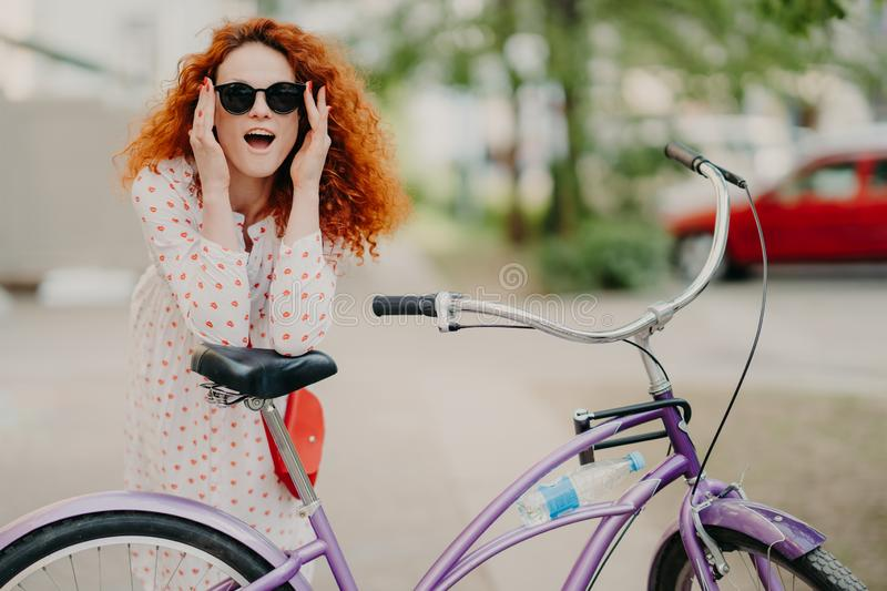 Happy woman has curly foxy hair, leans at saddle of her bicycle, has outdoor promenade during sunny summer day, wears stylish stock photos